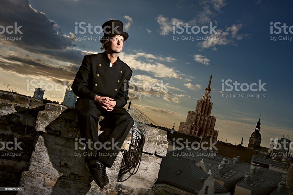 Chimney sweep sitting on the roof with city in background stock photo