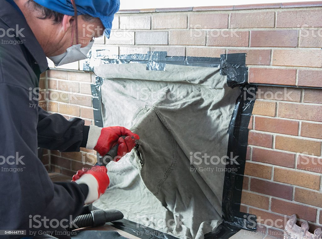 Chimney sweep wearing a mask for protection whilst cleaning chimney stock photo
