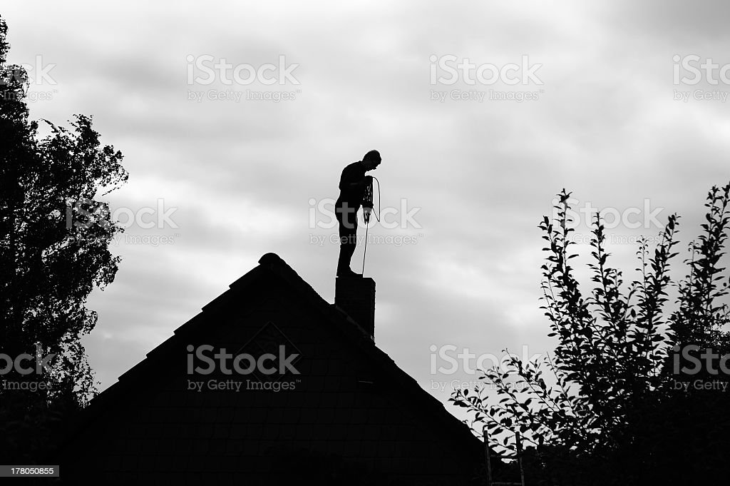 Chimney sweeper working on the roof stock photo