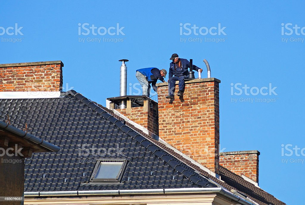 Chimney sweeps on the roof stock photo