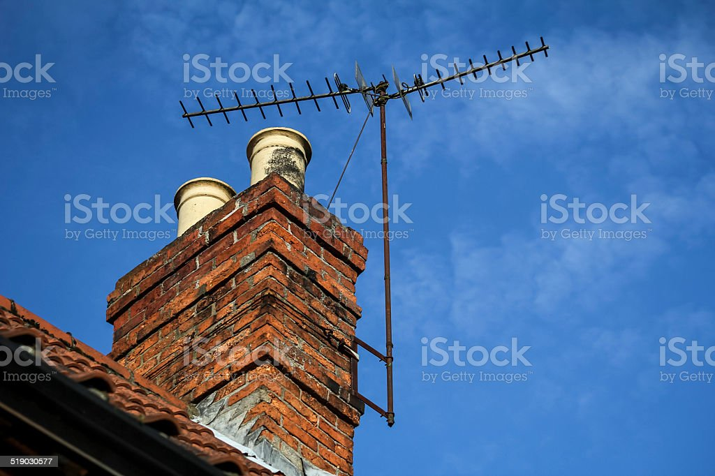 Chimney with TV aerial and blue sky with light cloud stock photo