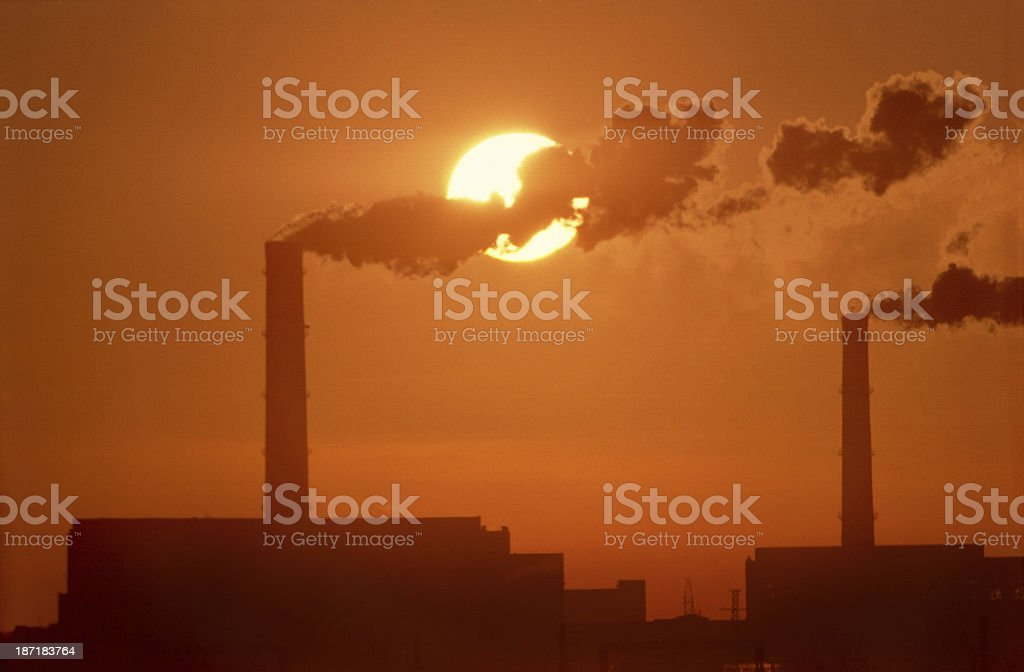Chimneys and smoke against the setting sun. royalty-free stock photo