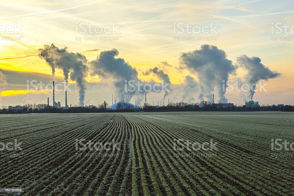 chimneys and smoke of industry plant with fields in sunrise royalty-free stock photo