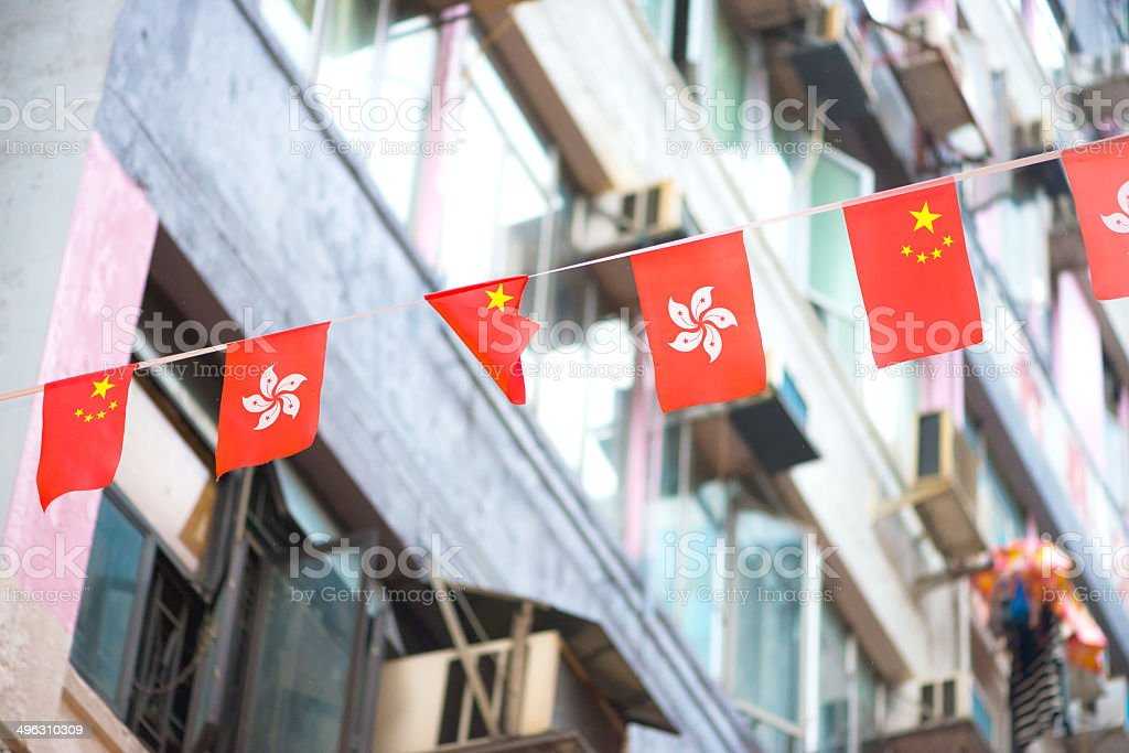 Chinese and Hong Kong Flags with Residential Building in Background stock photo