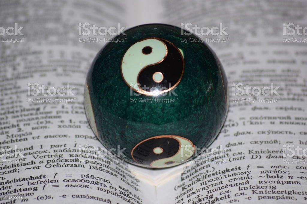 Chinese ball. Yin and Yang - the unity and struggle of opposites - the tiger and the dragon, black and white, love and hate. Chinese bowl and a book as a symbol of boundless knowledge. stock photo
