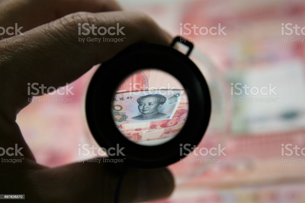 Chinese bank notes and loupe. stock photo
