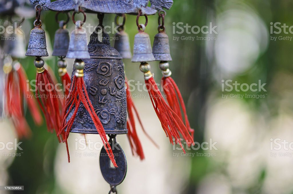Chinese bell and coin with red strings being blown outdoors stock photo