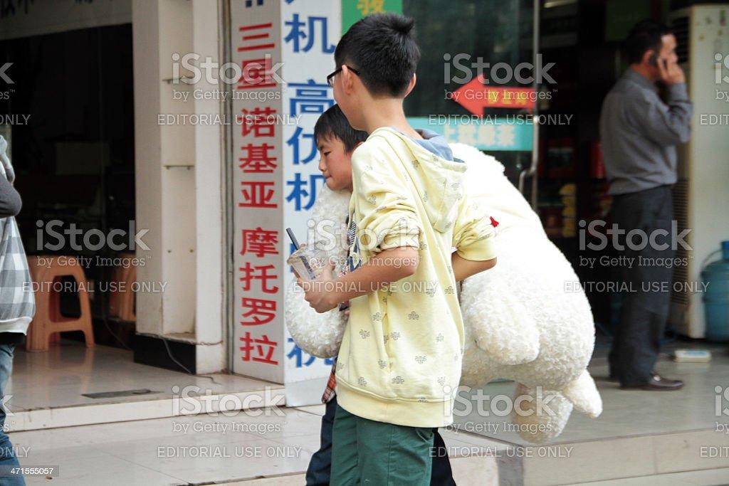 Ragazzo cinese che sta trasportando una grande Orsacchiotto foto stock royalty-free