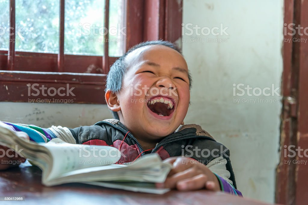 Chinese Boy with big laugh at school,looking away stock photo