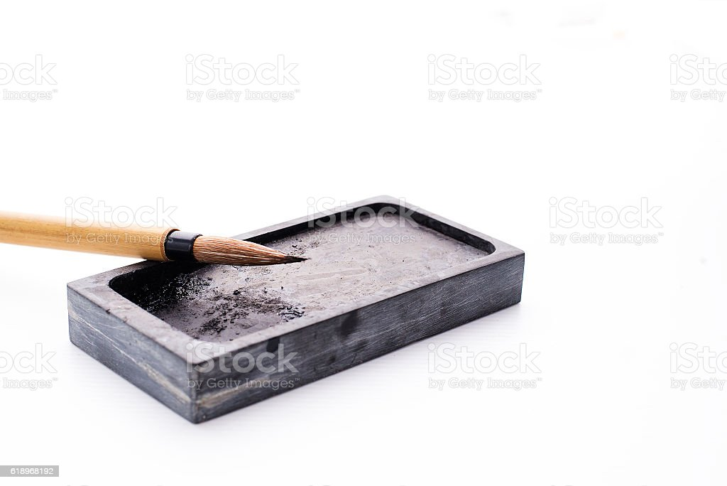 Chinese brushes and ink stone writing instrument on white papers stock photo