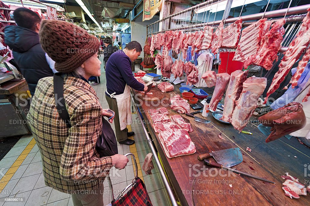 Chinese butcher chopping meat for customer market stall Hong Kong royalty-free stock photo
