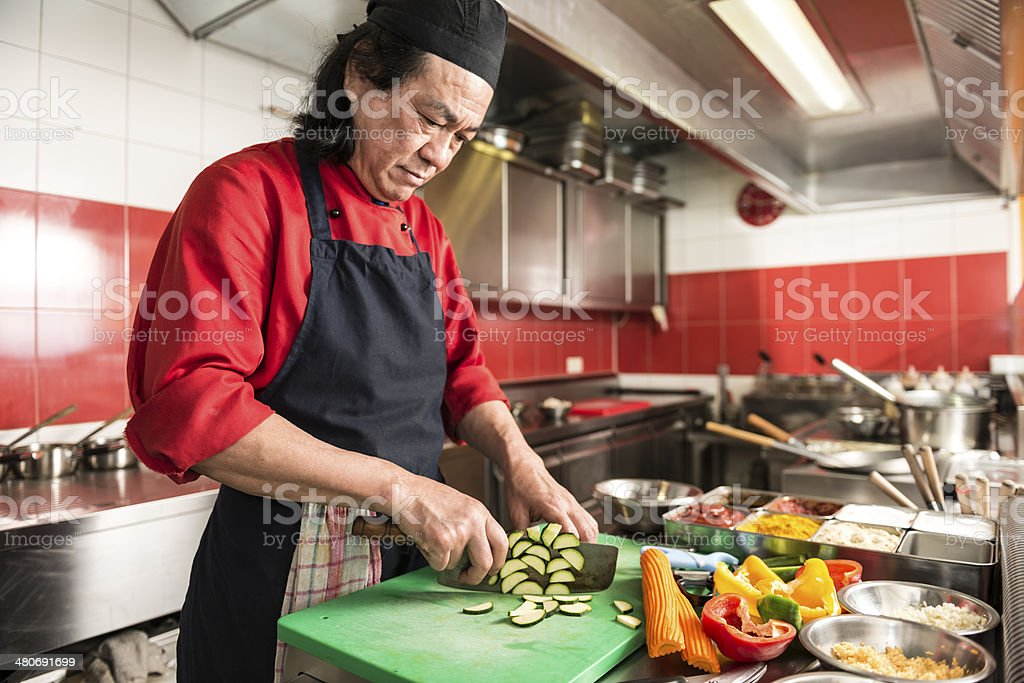 chinese cook cutting vegetables in asian restaurant stock photo