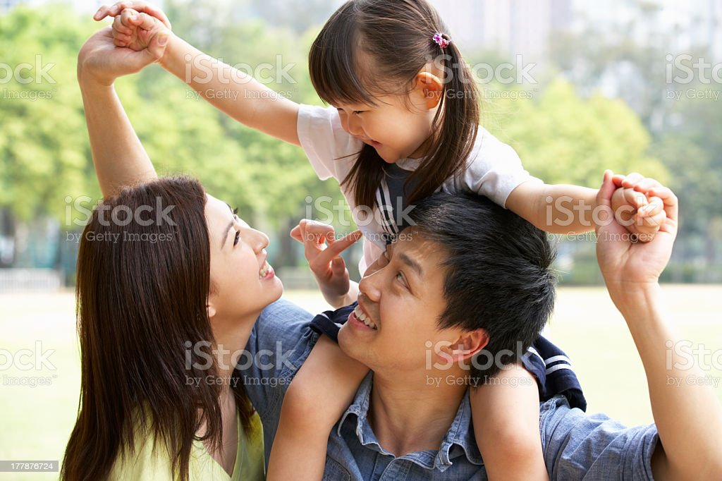 Chinese couple giving daughter a ride on shoulder in a park stock photo
