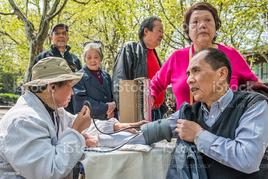 chinese doctor ausculting people in fuxing park shanghai china stock photo
