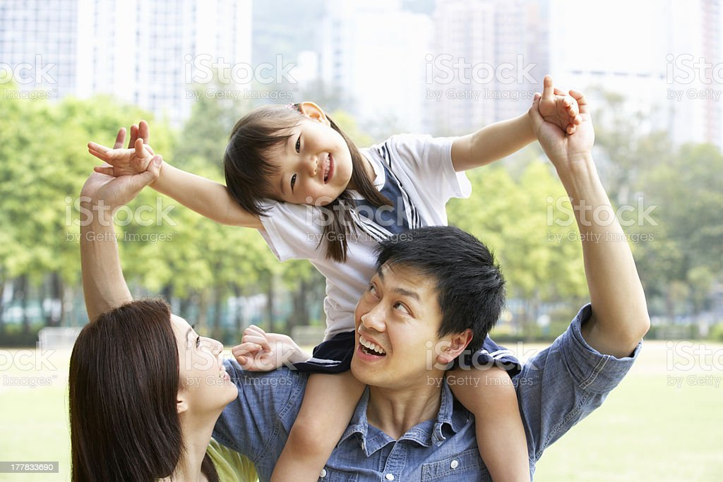 Chinese Family Giving Daughter Ride On Shoulders In Park royalty-free stock photo