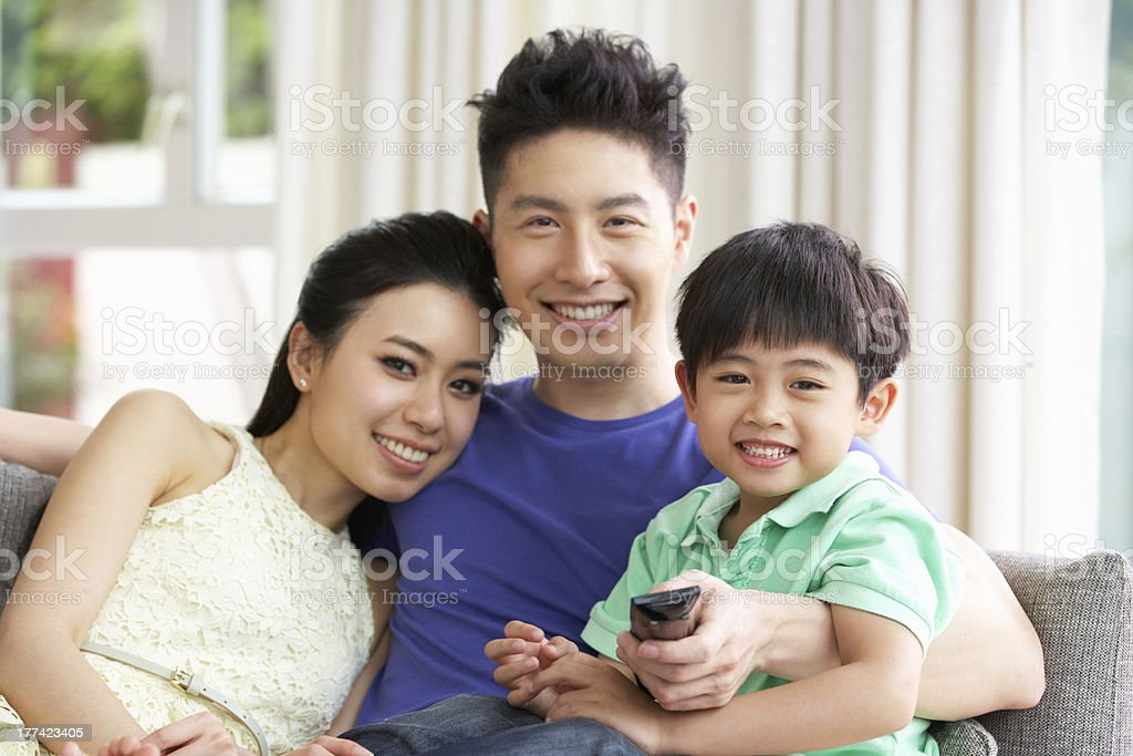 Chinese Family Sitting And Watching TV On Sofa Together royalty-free stock photo