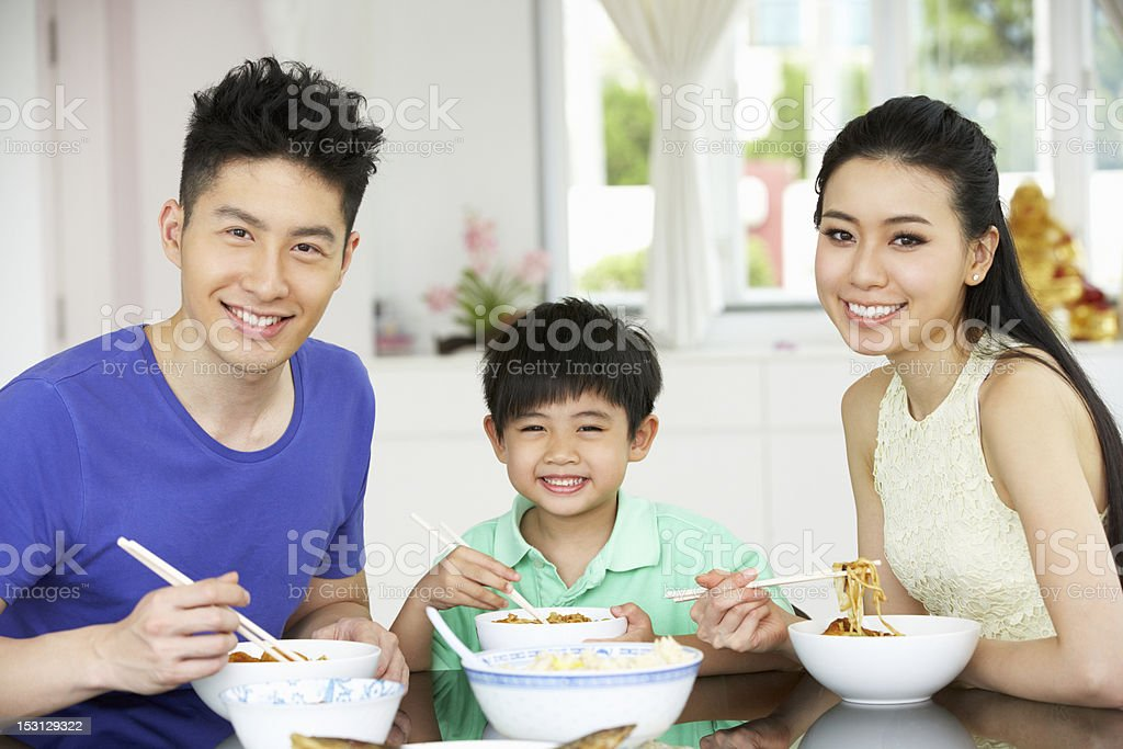 Chinese Family Sitting At Home Eating A Meal royalty-free stock photo