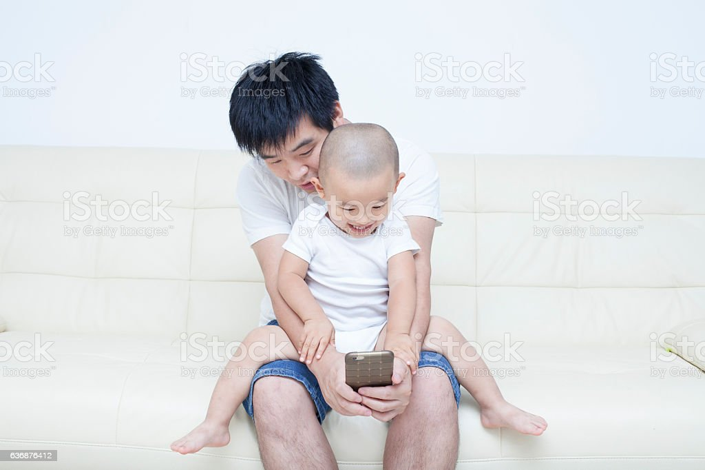 Chinese father and son taking selfie in sofa stock photo