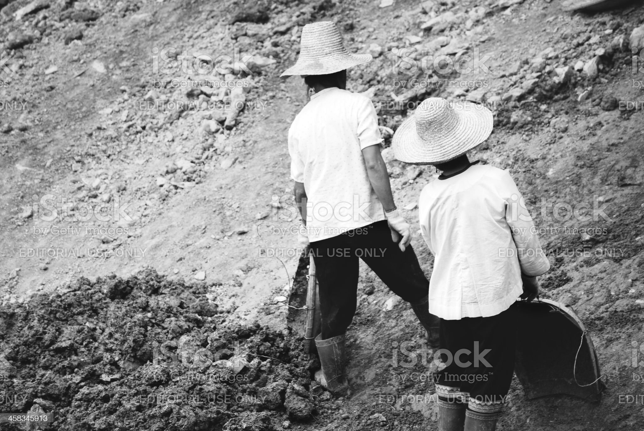 Chinese female farm workers are preparing soil for rice terraces royalty-free stock photo