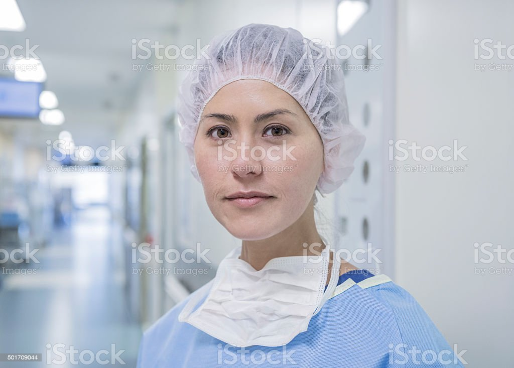 Chinese female surgeon wearing surgical cap in hospital corridor stock photo