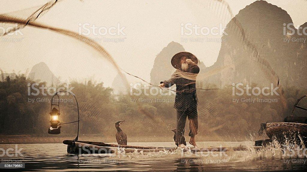 Chinese fisherman throwing net on river Li stock photo