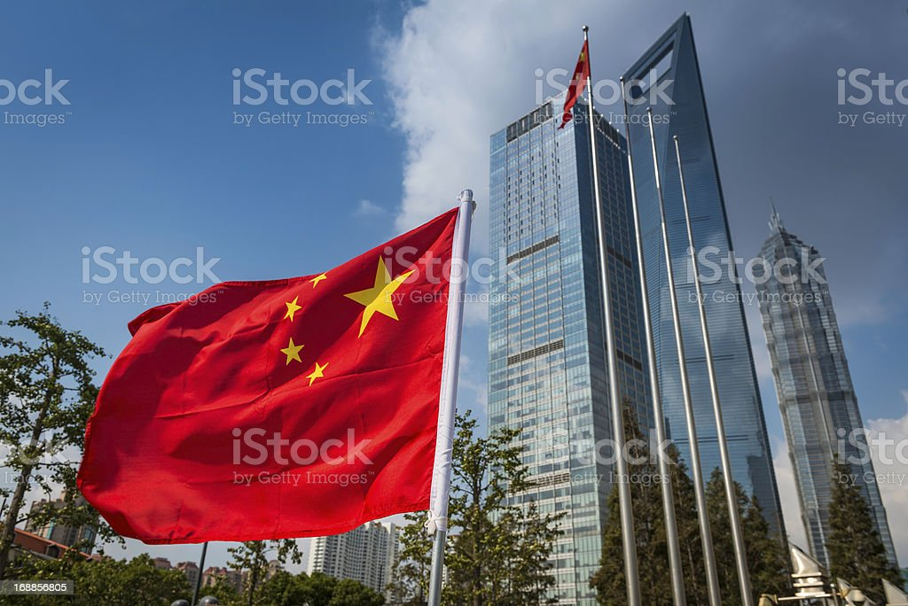 Chinese flag flying beside futuristic Shanghai skyscrapers stock photo