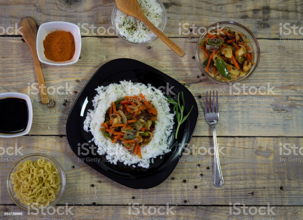 Chinese food on the plate with spices on a wooden background stock photo