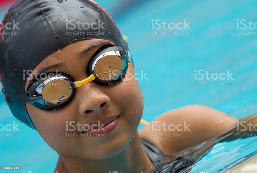 Chinese girl smiles in a black swim cap stock photo