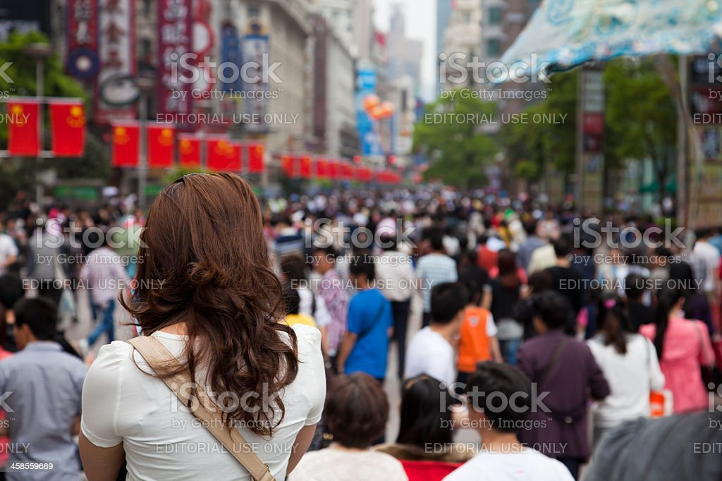 Chinese girl standing in front of a crowd, Shanghai, China royalty-free stock photo