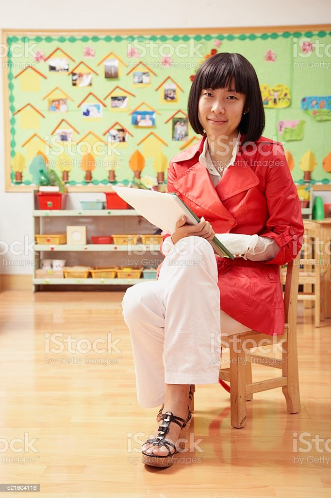 Chinese grade school teacher in classroom stock photo