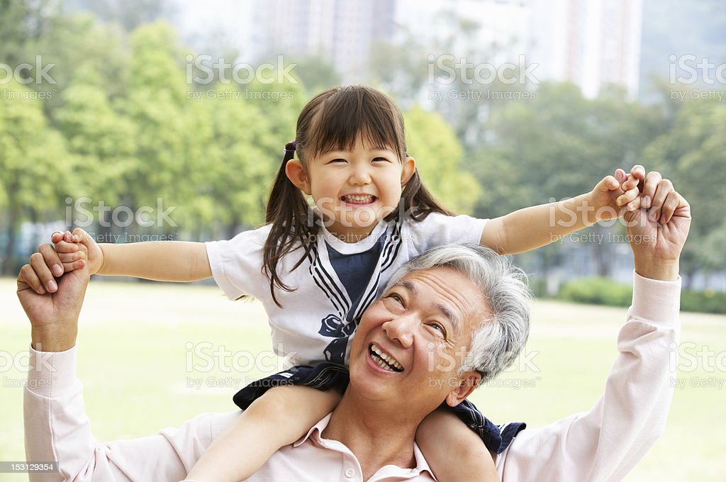 Chinese Grandfather Giving Granddaughter Ride On Shoulders stock photo
