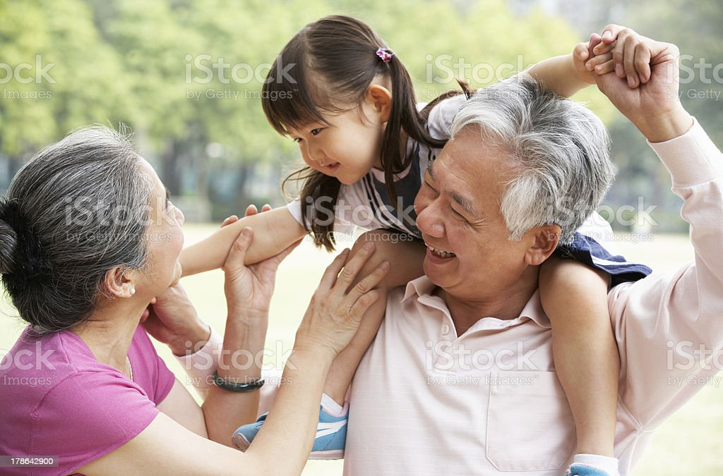 Chinese Grandparents Giving Granddaughter Ride On Shoulders stock photo