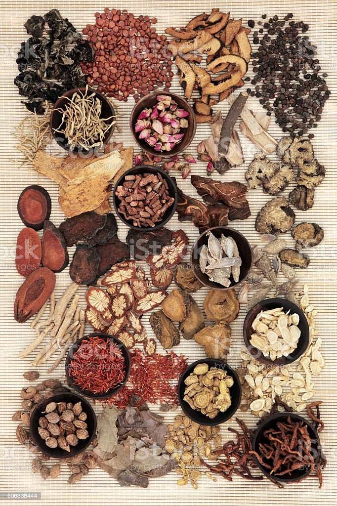 Traditional chinese herbal medicine in wooden bowls and loose over...