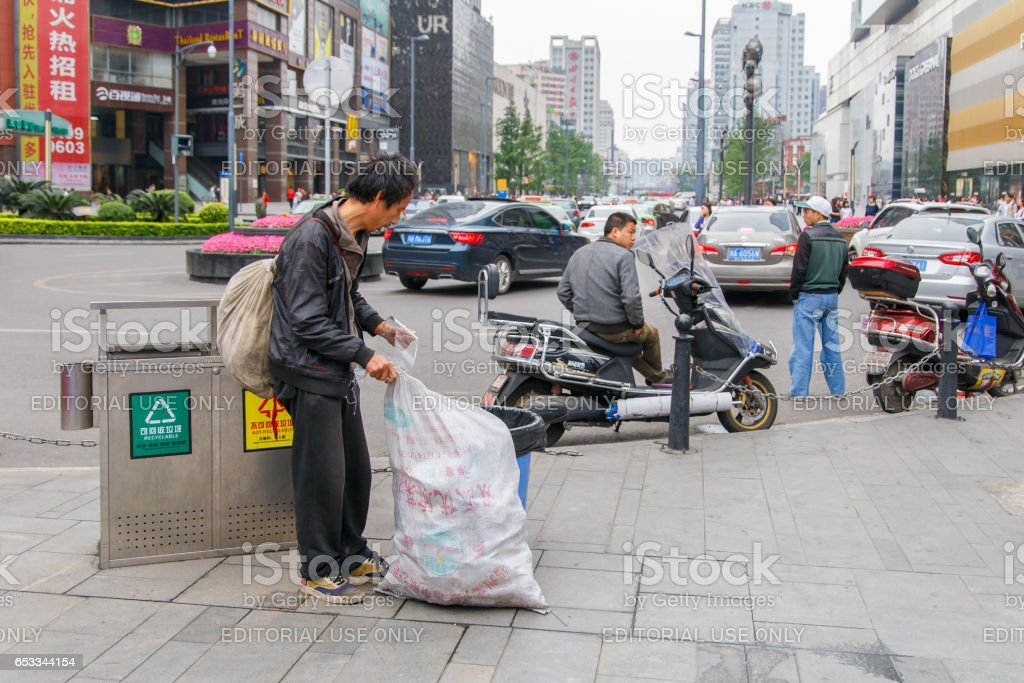 CHENGDU, CHINA - MAY 8, 2016: Chinese homeless looks for food and valuable in a garbage tin on May 8 2016 in Chengdu, China stock photo
