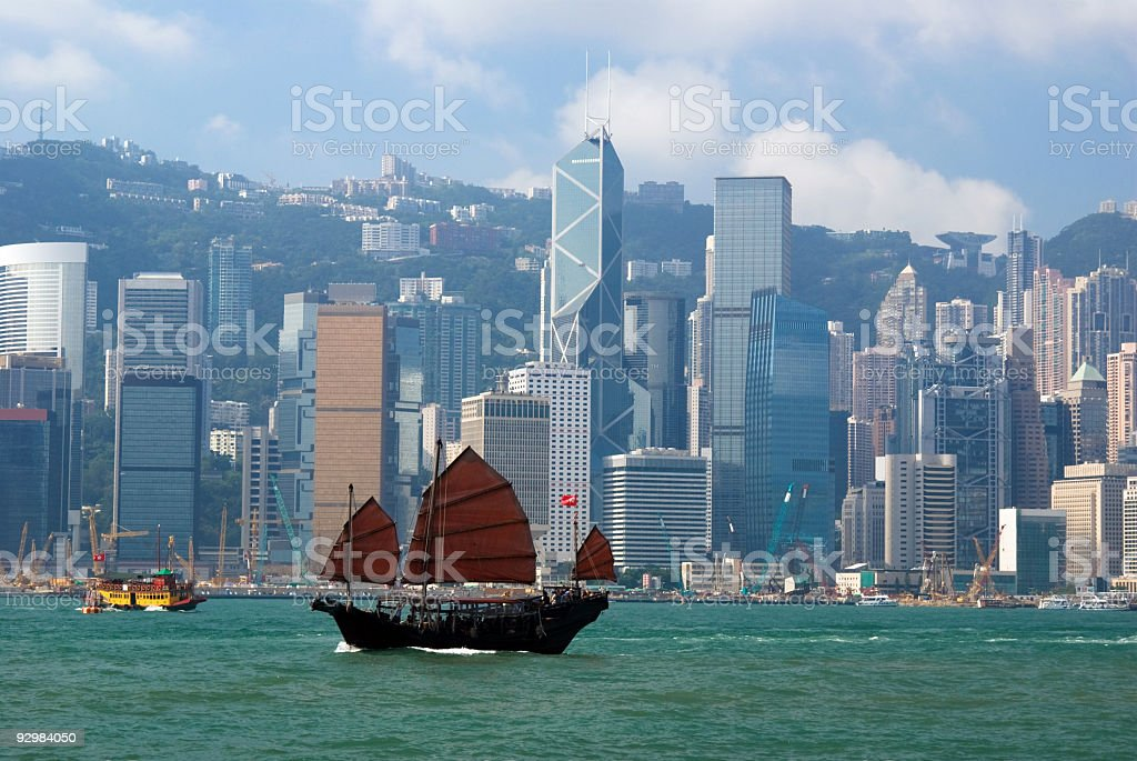 Chinese junkboat sailing across Hong Kong harbor stock photo