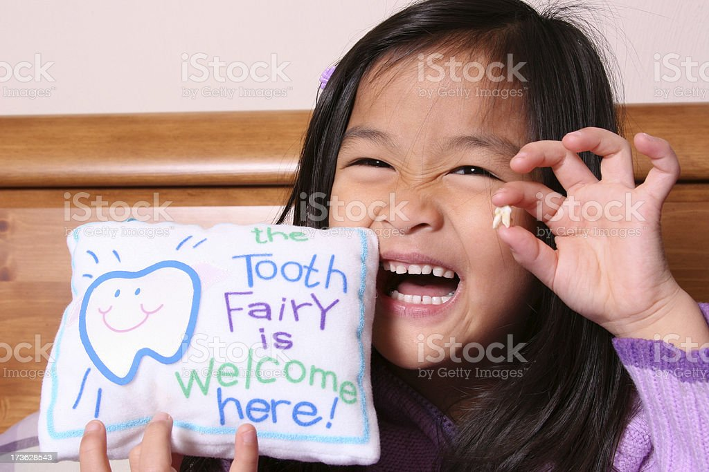 Chinese little girl holding up her tooth royalty-free stock photo