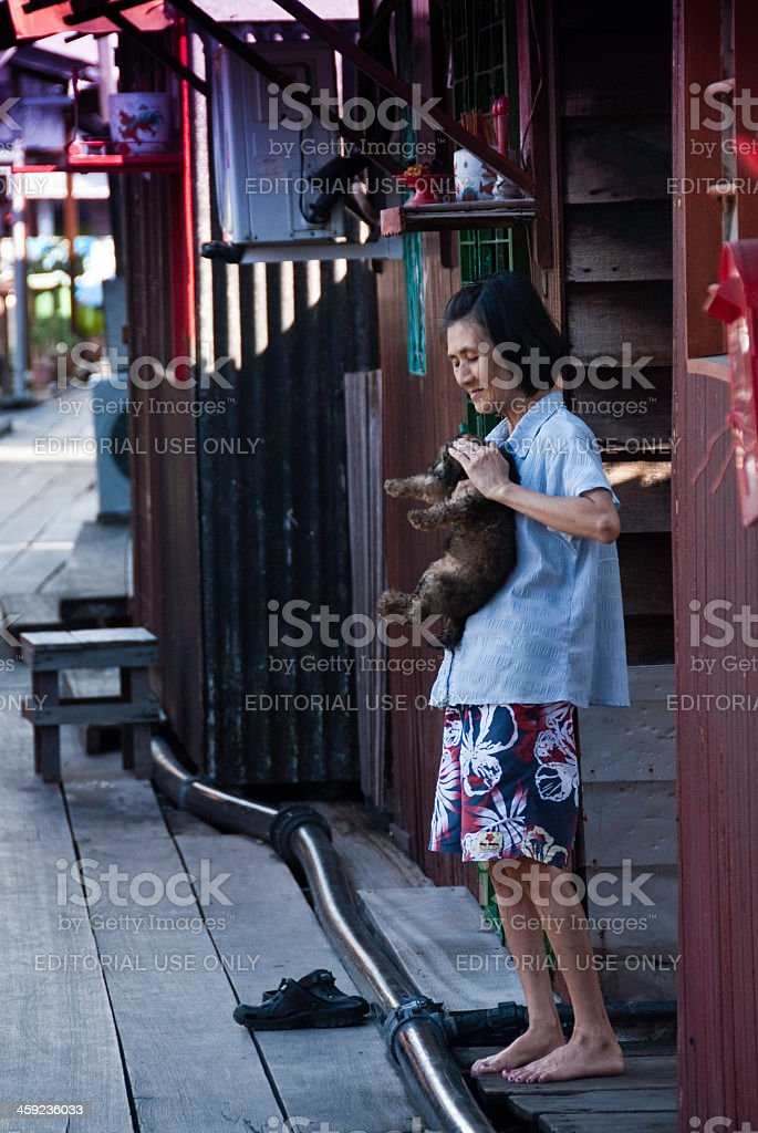 Chinese Malaysian women outside her home with puppy royalty-free stock photo