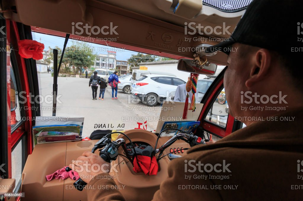 Chinese man driving a tuk tuk inside the old town of Dali, the ancient kingdom of Nanzhao stock photo