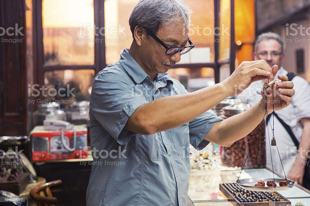 Chinese Man Weighs Herbs in Kowloon Medicine Shop Hong Kong stock photo