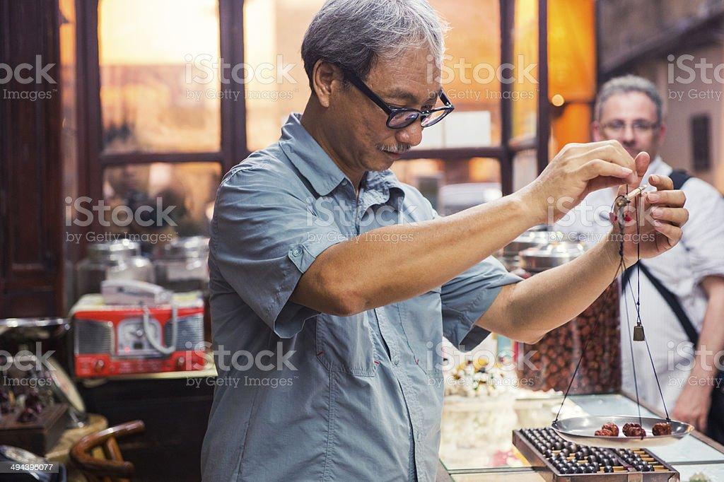 Chinese Man Weighs Herbs in Kowloon Medicine Shop Hong Kong stock photo