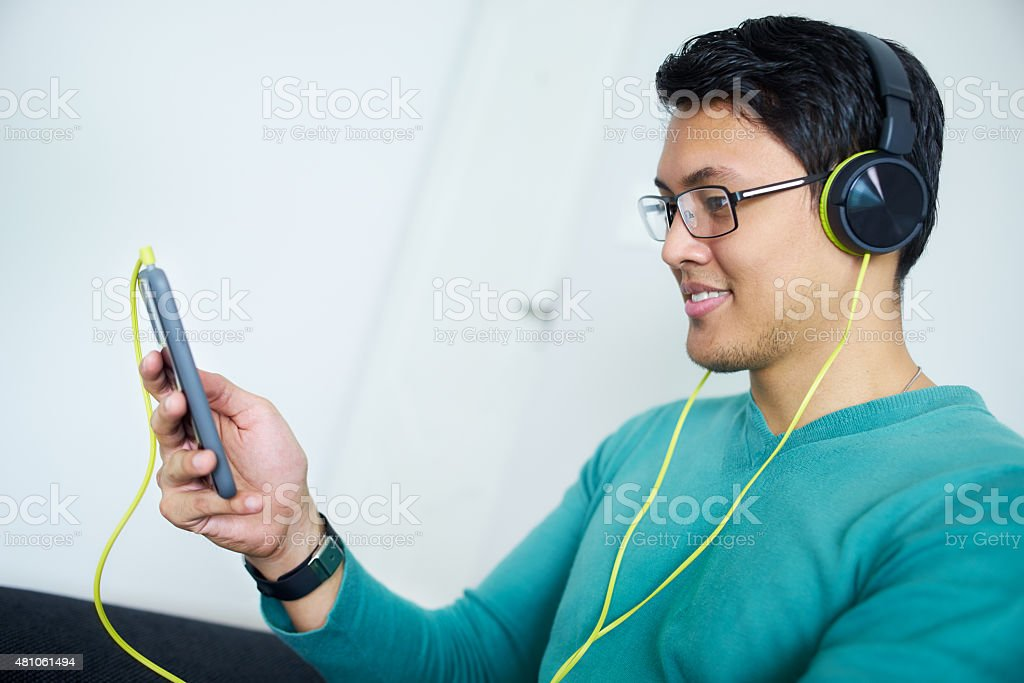 Chinese Man With Green Headphones Listens Podcast Phone At Home stock photo