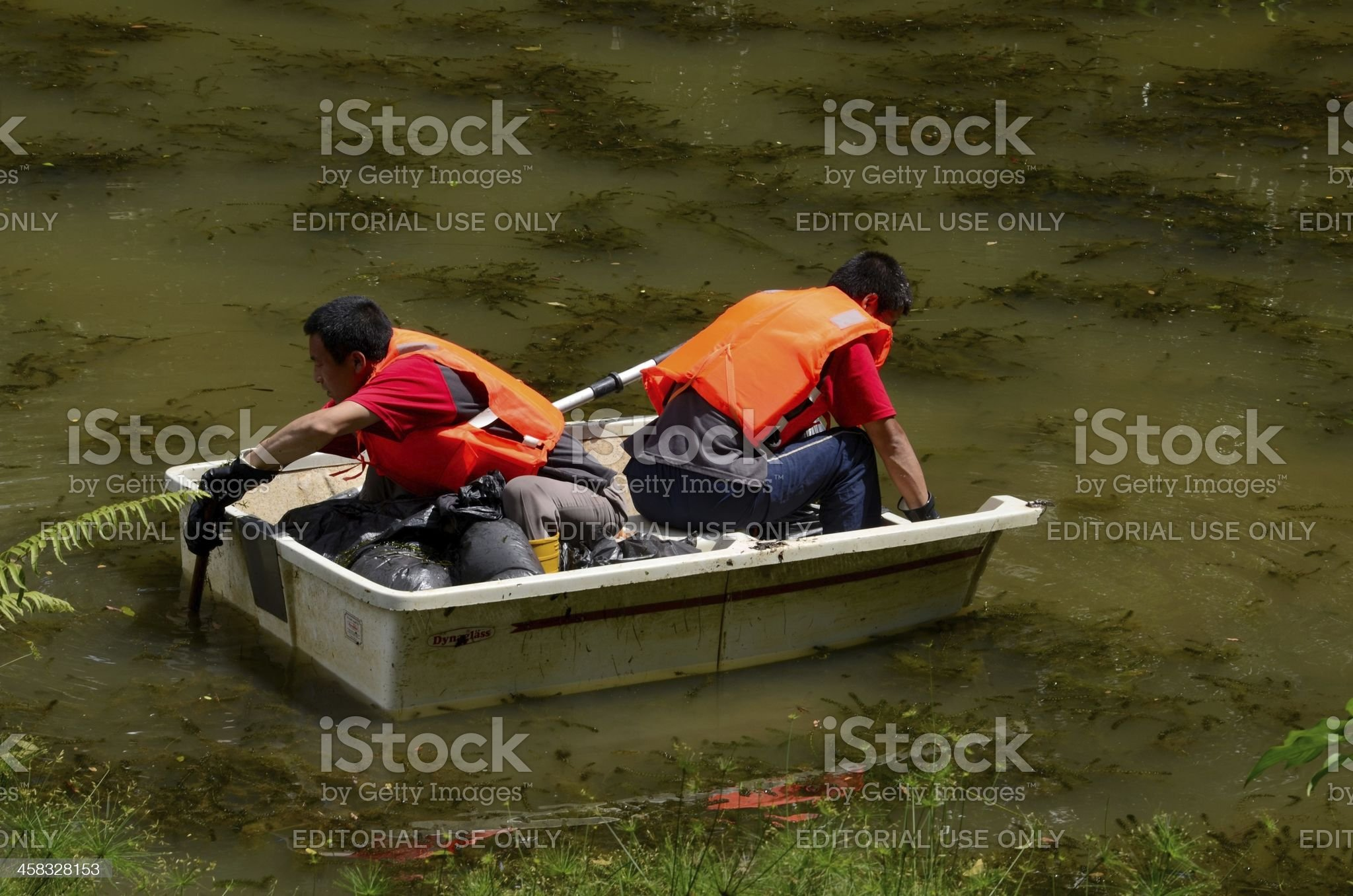 Chinese men in white boat clean lake, Singapore royalty-free stock photo