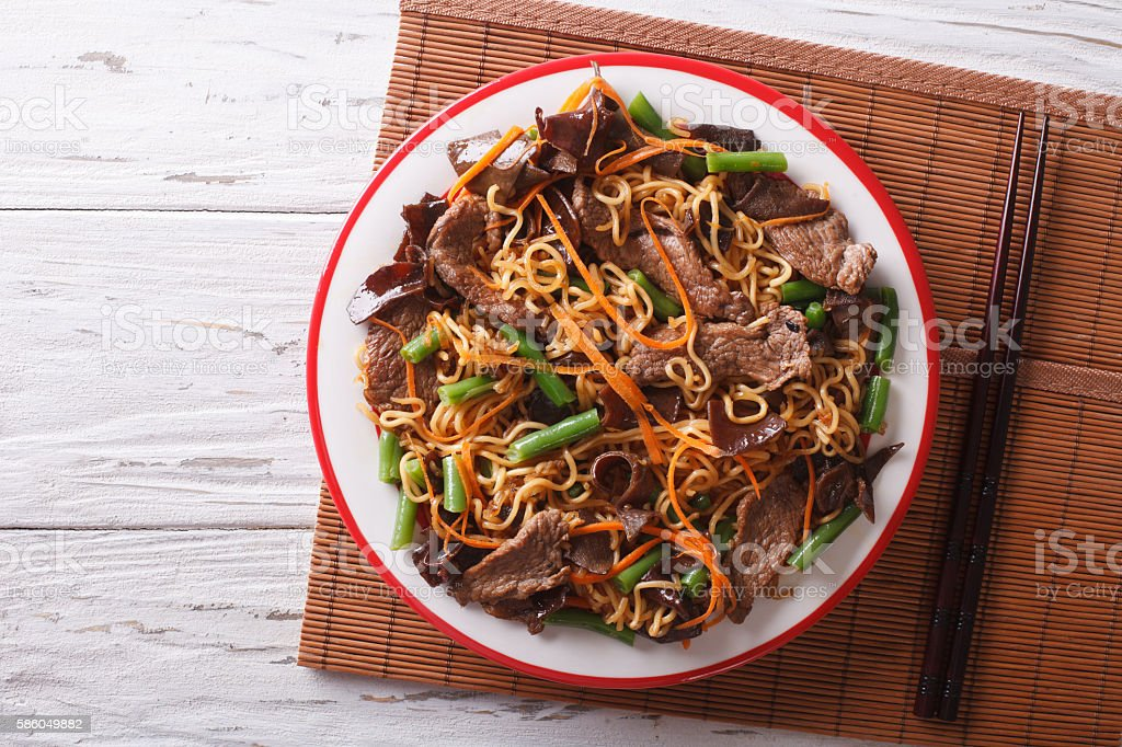 Chinese noodles with beef, muer and vegetables. Horizontal top view stock photo