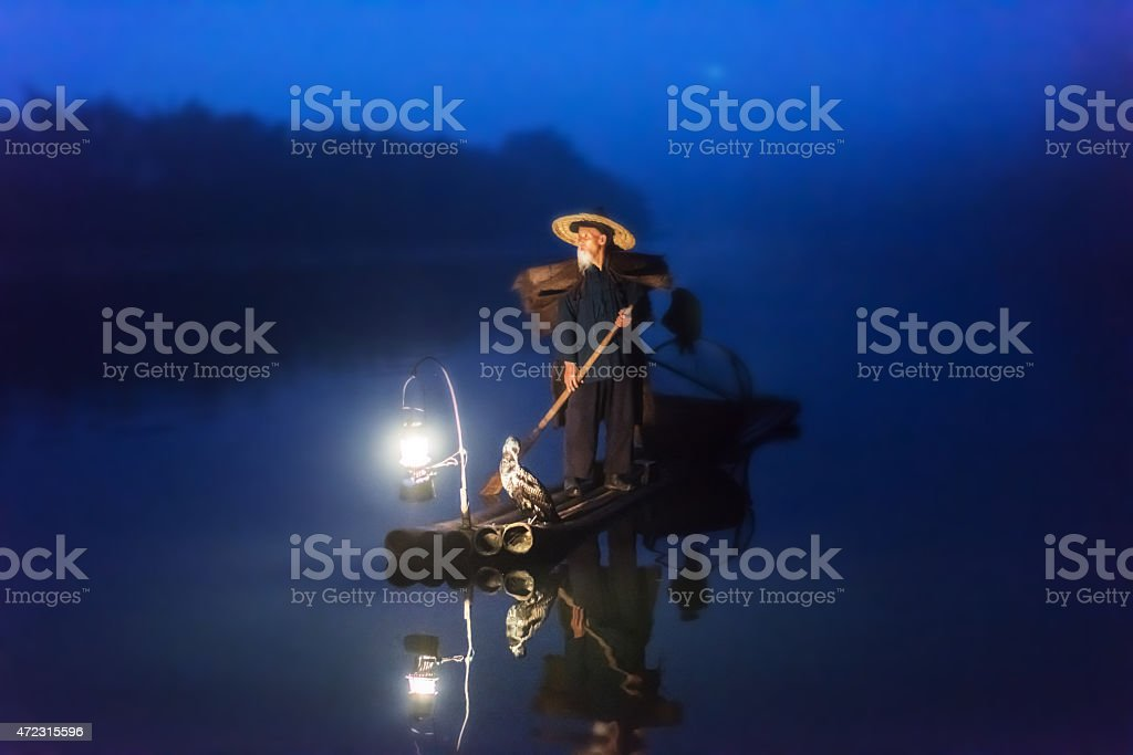 Chinese old senior fisherman on wooden raft fishing Li River stock photo