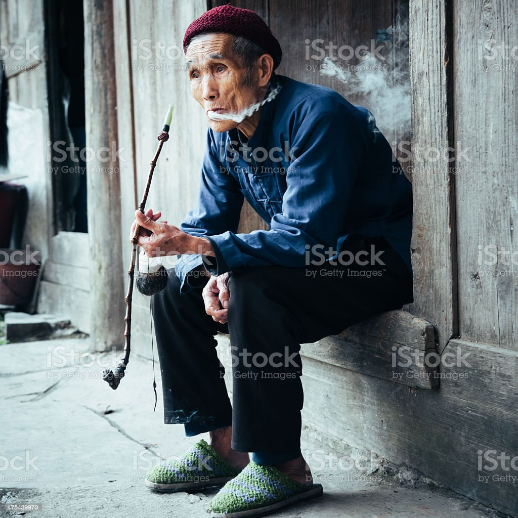 Chinese old senior man smoking pipe at his homedoor stock photo