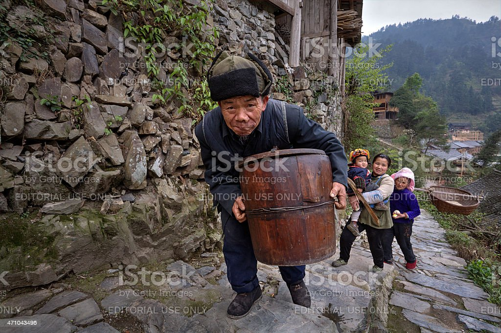 Chinese older man climbs stone mountain road with wooden barrel stock photo