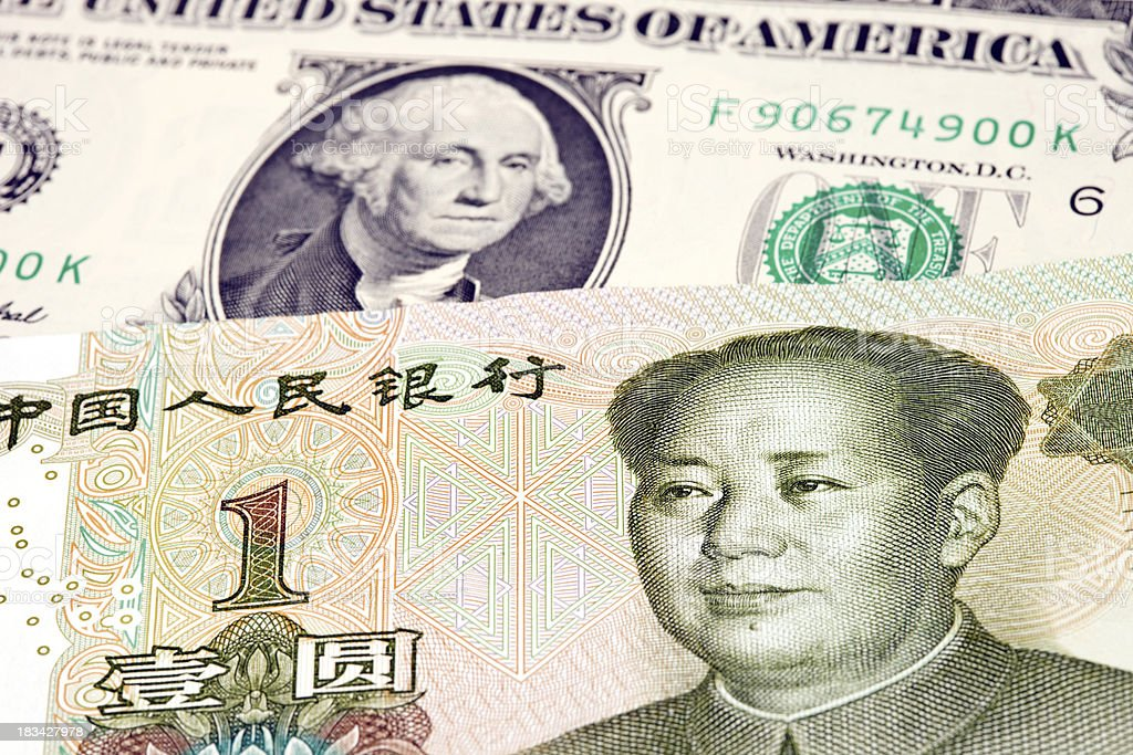 Chinese One Yuan Rests on top of US Dollar stock photo