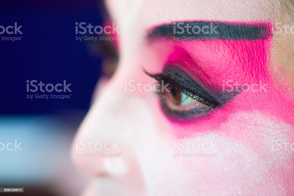 Chinese opera actress is painting mask on her face before the performance stock photo