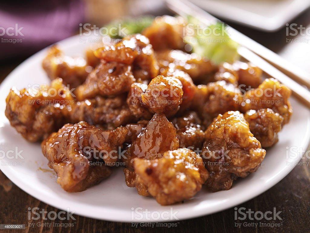 chinese orange chicken with chopsticks stock photo