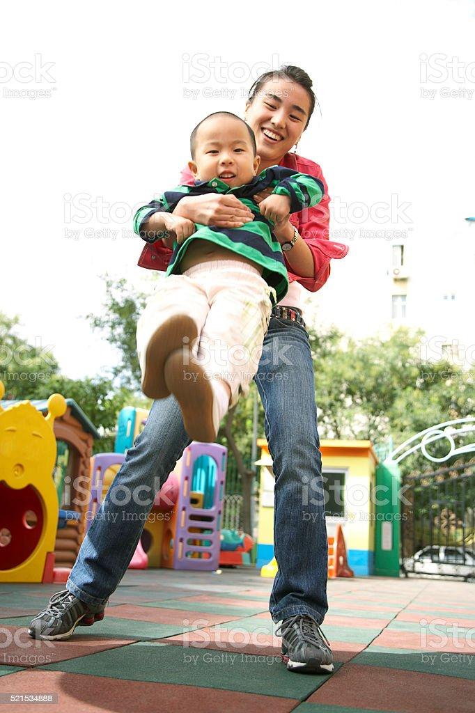 Chinese parent swinging child in playground stock photo